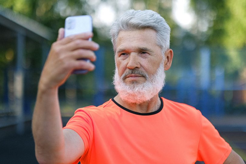 serious aged man taking selfie on smartphone