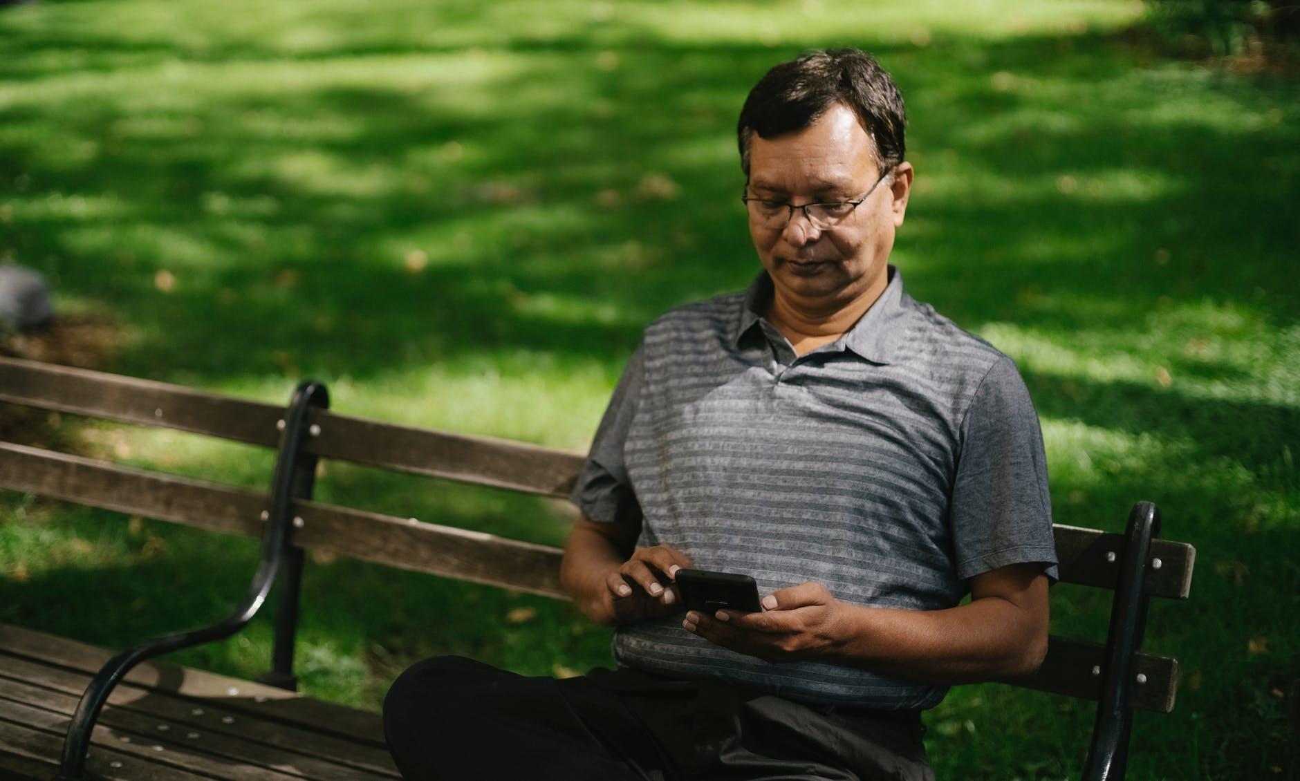 man surfing net sitting on bench