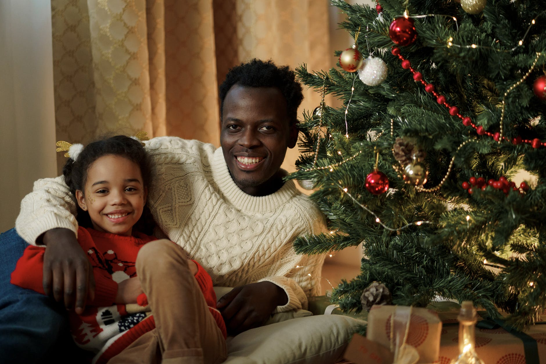 dad and daughter smiling at the camera beside a christmas tree