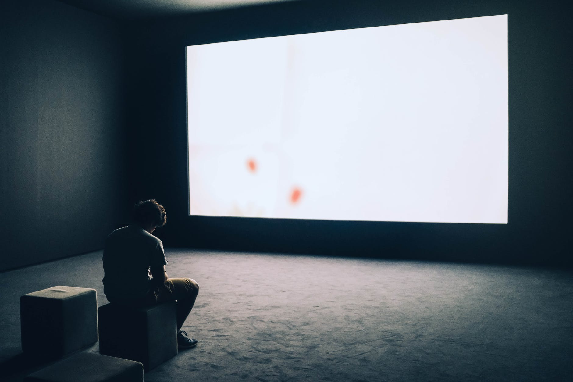 man sitting in front of turned on screen