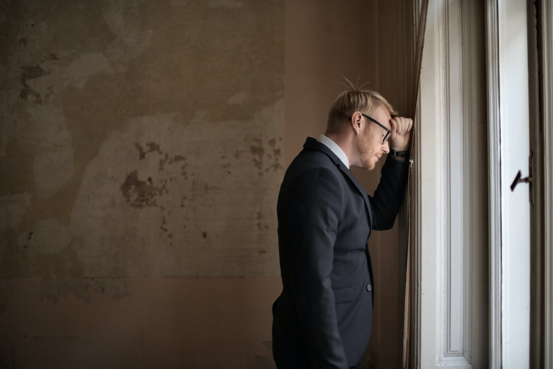 desperate evicted male entrepreneur standing near window