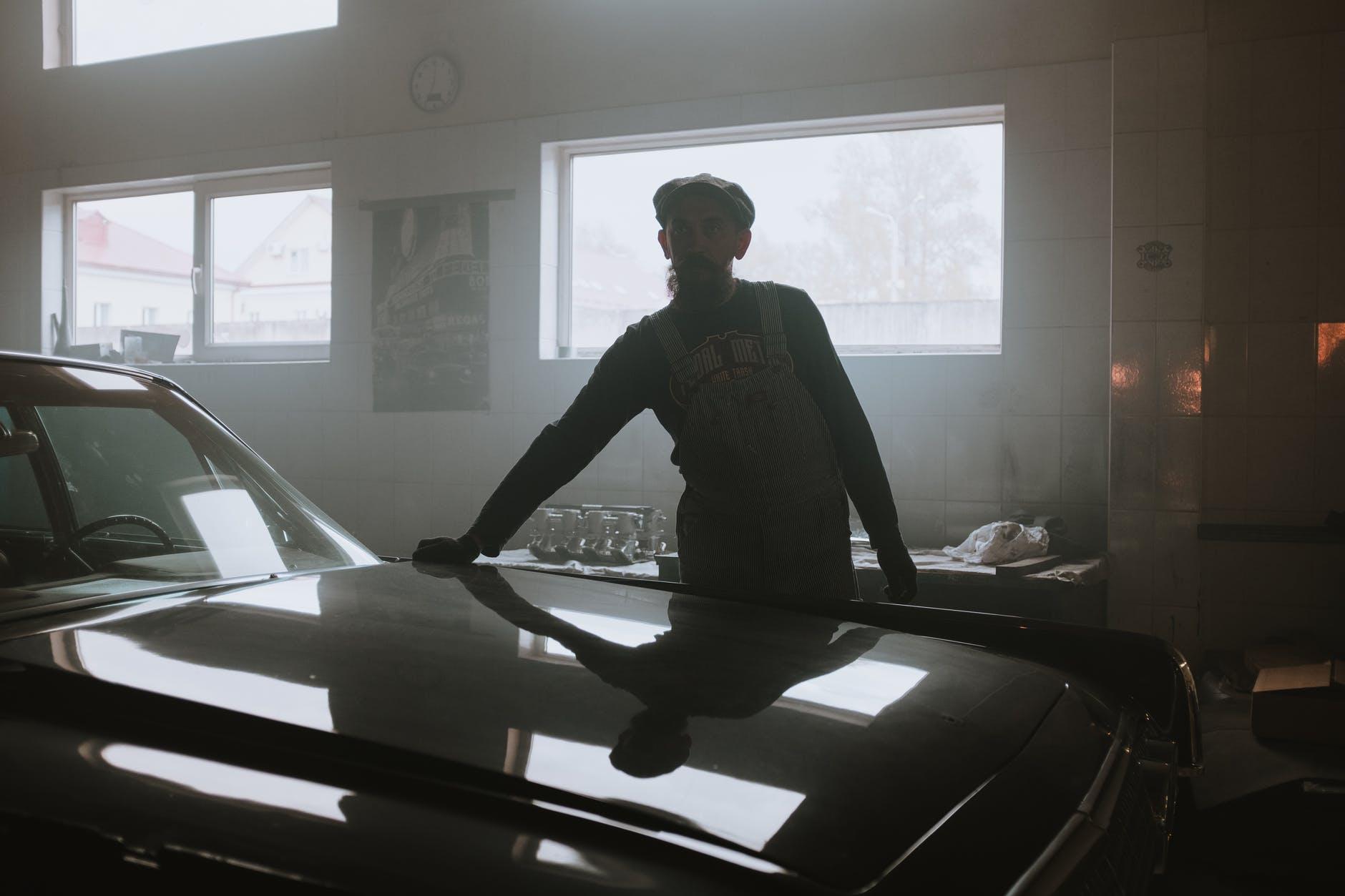 man in black jacket standing near window