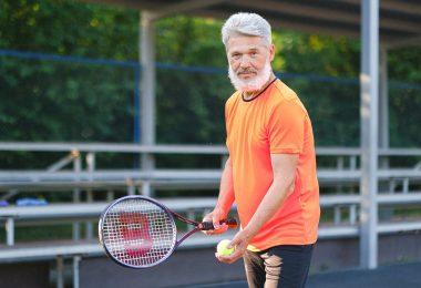 cheerful senior man playing tennis on street