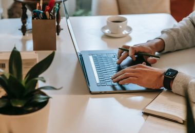 faceless male freelancer using netbook near coffee cup and notepad