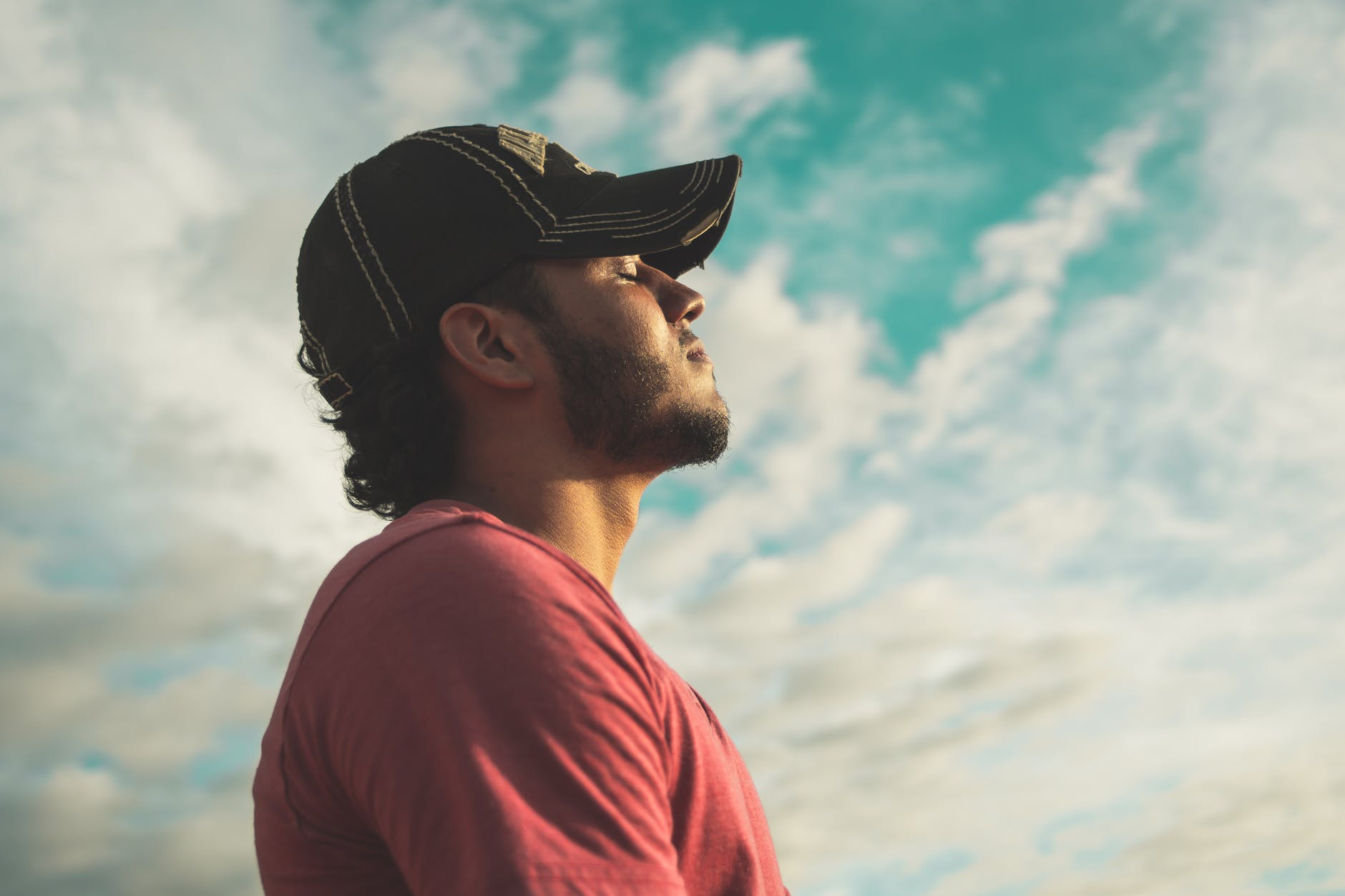 man wearing black cap with eyes closed under cloudy sky