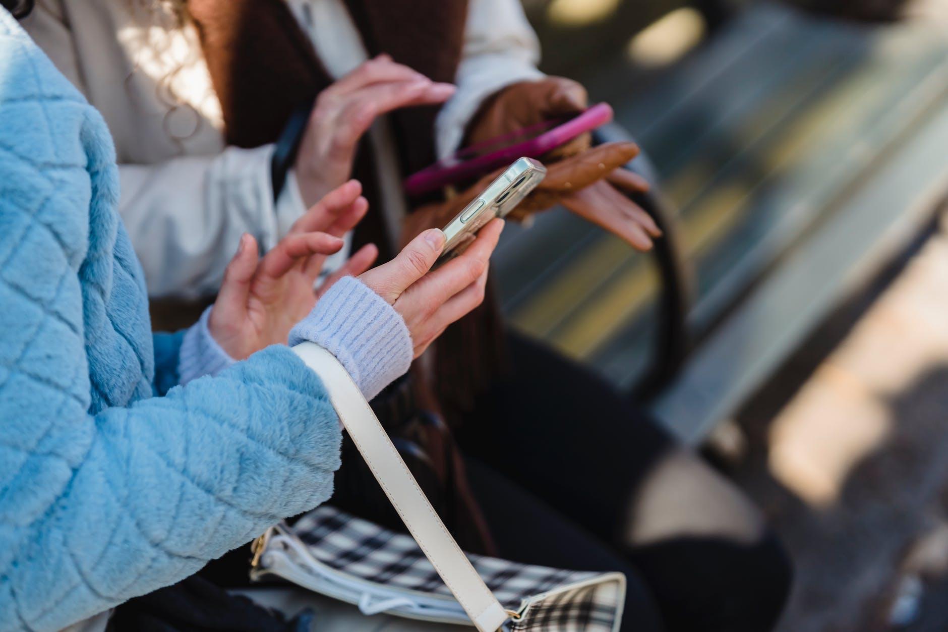 women touching screens of smartphones in park