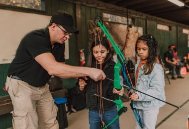 cute attentive diverse little girl practicing archery with male instructor