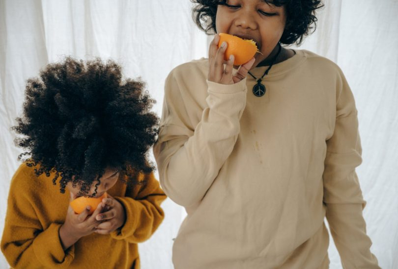 hungry ethnic kids with fresh fruit in studio