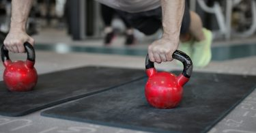 muscular sportsman doing plank exercise on kettlebells