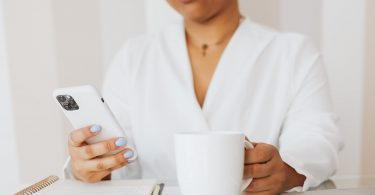 person in white top holding white ceramic mug while using cellphone