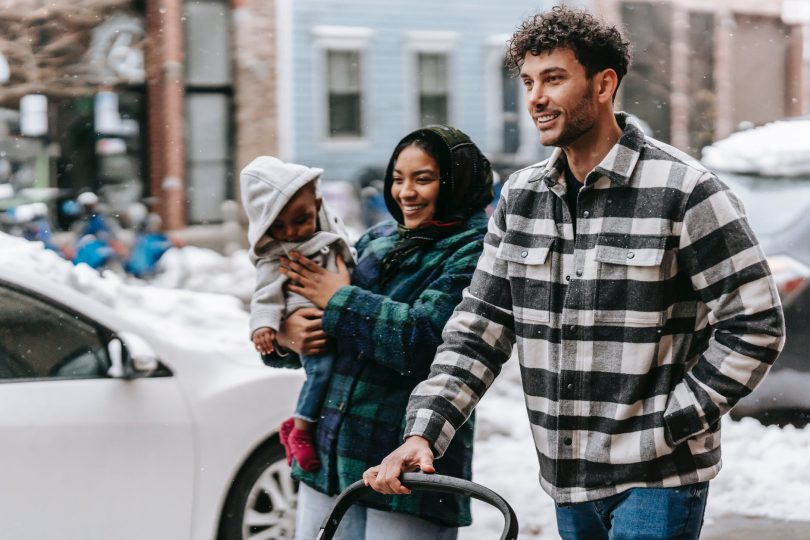 cheerful young diverse family with toddler strolling on street and smiling