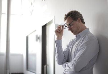 photo of man holding black eyeglasses