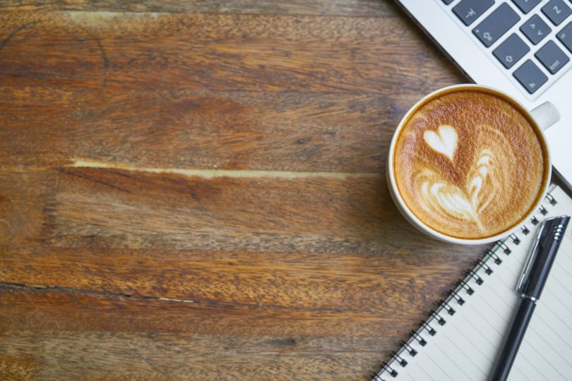 cup of fresh cappuccino near laptop keyboard and notebook