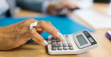 person holding gray desk calculator